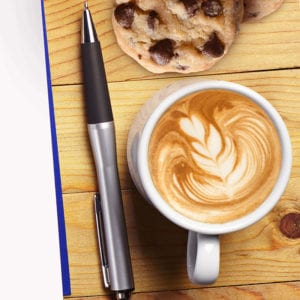 Pen on wooden background with coffee and chocolate chip cookies.